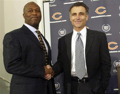 NEW CHICAGO BEARS HEAD COACH LOVIE SMITH SHAKES HANDS WITH GENERAL MANAGER JERRY ANGELO.