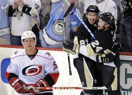 Pittsburgh Penguins Miroslav Satan celebrates his goal with teammate Matt Cooke as Carolina Hurricanes Joni Pitkanen skates away during the