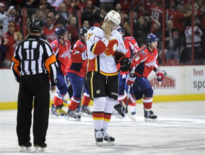 Flames' Bourque reacts as the Capitals celebrate Ovechkin's goal during their NHL hockey game in Washington.