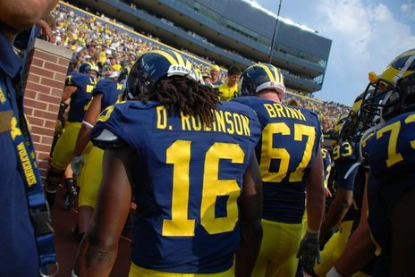 Denard Robinson and other Michigan players leave Michigan Stadium earlier this season.
