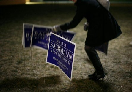 A supporter of Republican presidential candidate Michele Bachmann places signs in support of Bachmann outside the 2012 Iowa Caucus site at W