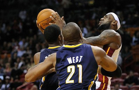 Miami Heat's LeBron James is defended by Indiana Pacers's George and West during their NBA basketball game in Miami.