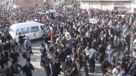 Demonstrators wait for the arrival of Arab League observers in Deir Balaba