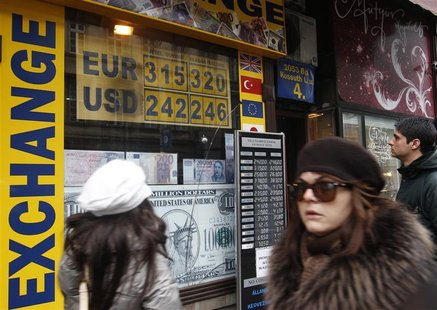 People walk past a currency exchange shop in Budapest