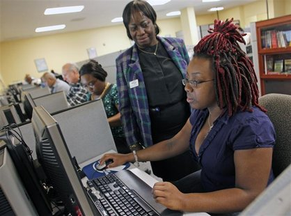 Smith fills out an online job application with the help of career consultant Coleman at the Workforce Alliance Career Center in West Palm Be