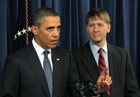 President Barack Obama speaks as Richard Cordray, his appointed head of the Consumer Financial Protection Bureau, stands at his side during