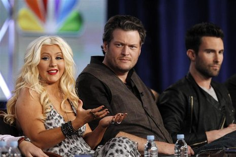 "Aguilera answers a question as Shelton and Levine watch during the panel for the NBC television series ""The Voice"" in Pasadena."