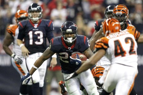 Houston Texans' Foster runs with the ball between Texans quarterback Yates and Cincinnati Bengals' Crocker in the third quarter during their