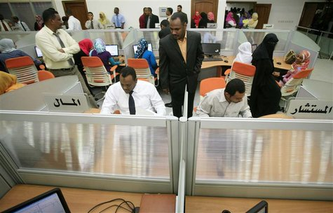 Traders work during the opening of the new electronic trading Khartoum Stock Exchange