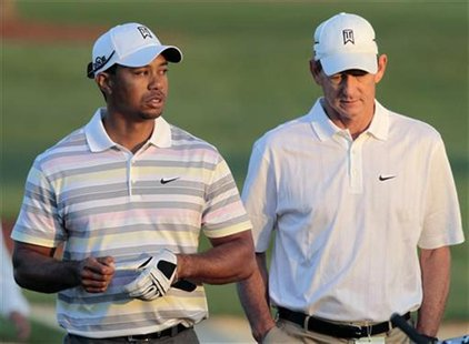 Woods of the U.S. walks off the driving range with his swing coach Haney before his practice round for the 2010 Masters golf tournament at t