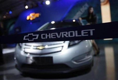 A model stands besides a GM Chevrolet Volt car during India's Auto Expo in New Delhi