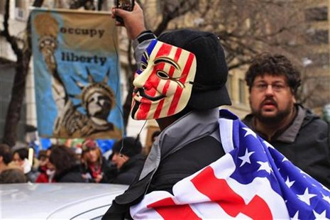 Protesters, one in a Guy Fawkes mask, affiliated with the Occupy Wall Street movement, protest around Duarte Square in New York