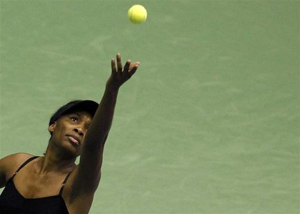 Venus Williams of the U.S. serves to Flavia Pennetta of Italy during an exhibition tennis match in Milan