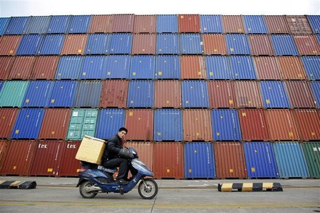 A man rides his motorcycle past shipping containers at the Port of Shanghai