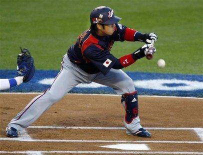 Team Japan's Hiroyuki Nakajima bunts against Team Korea during the first inning of their World Baseball Classic championship game in Los Ang
