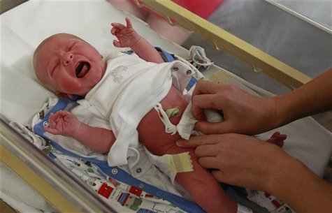 Newborn baby boy is examined by a paediatrician in the maternity ward in Huntingdon