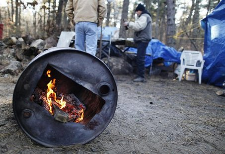 Two men talk while warming themselves by a fire in a homeless community near Lakewood, New Jersey