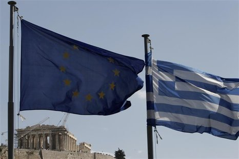 A European Union and Greek flag wave in front of the Parthenon temple in Athens