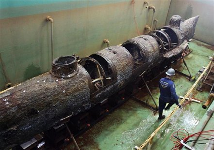 A member of the conservation crew walks beside the Civil War submarine H.L. Hunley as it now stands free of the steel truss that was used to
