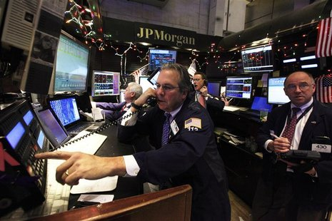 Specialists and traders work at the JP Morgan stall on the floor of the New York Stock Exchange