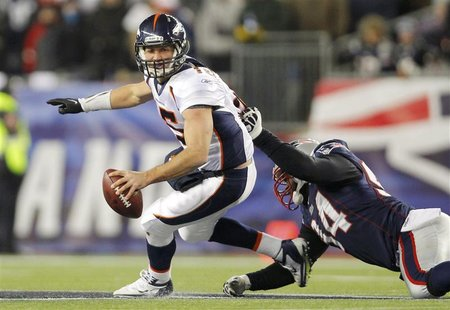 Denver Broncos quarterback Tim Tebow (L) is grabbed by New England Patriots defensive end Shaun Ellis in the third quarter of their NFL AFC
