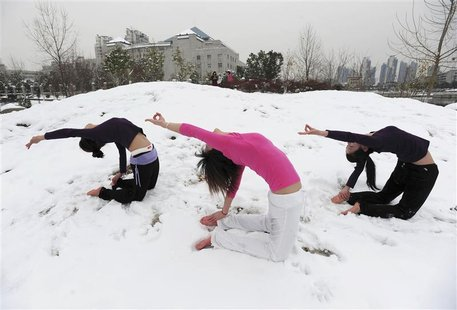 Local residents practise yoga after a snowfall at a park in wuhan