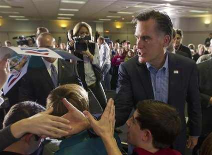 Republican presidential candidate Romney shakes hands with supporters during a campaign stop in Sumpter