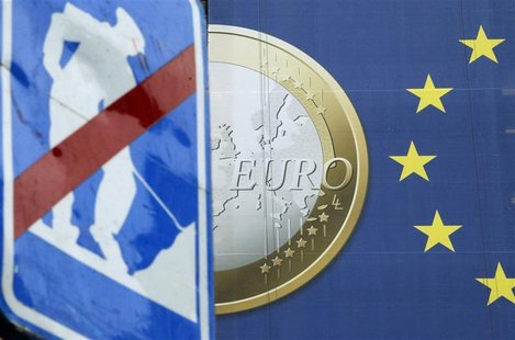A road sign is seen near a banner of a euro coin on the facade of the European Commission headquarters in Brussels