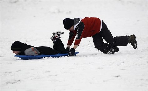 Seattle residents Moore pushes friend Clement on sled in Maple Leaf Park in Seattle.