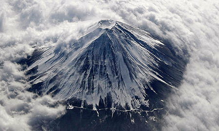 Snow-covered Mount Fuji peeks through miles of fluffy clouds  At 3,776 metres high, it is Japan's highest peak   Courtesy: Reuters
