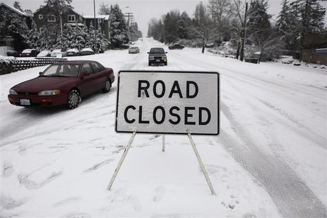 Several vehicles ignore a road closure on a hill in Kirkland, Washington