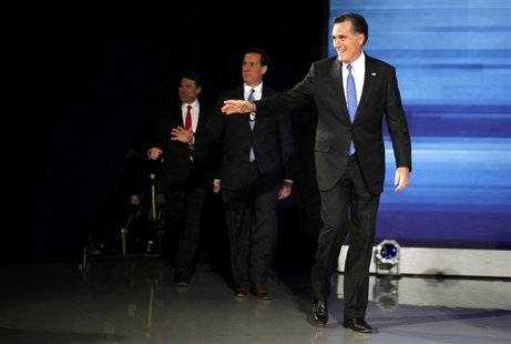 Republican presidential candidates Romney, Santorum and Perry arrive on stage to participate in a Republican presidential candidates debate
