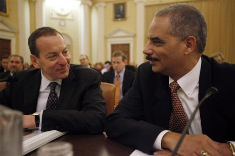 U.S. Attorney General Holder chats with Assistant Attorney General Breuer before their testimony on the second day of the Financial Crisis I