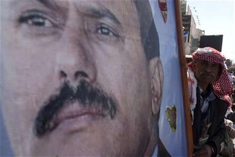 A supporter of Yemen's outgoing President Ali Abdullah Saleh holds his poster as they attend a rally to show support for Saleh in Sanaa