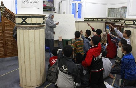 A teacher and volunteer from the Muslim Brotherhood revises lessons for free with school pupils before their exams, at a mosque in Alexandri