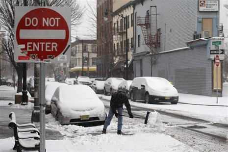 A man cleans the street during a snow storm in Jersey City