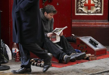 A pedestrian passes a man sat waiting at a shoe shine stall in the City of London