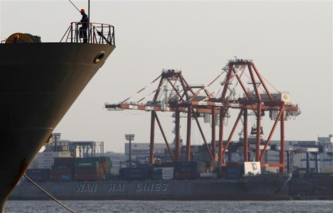 A worker stands on a ship in front of a cargo ship at a port in Tokyo