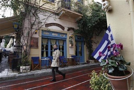 A man walks in front of a cafe at Plaka tourist district in Athens