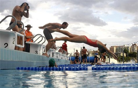 Participants jump into a swimming pool during a weekly, after-work biathlon at The Domain adjacent to Sydney's central business district