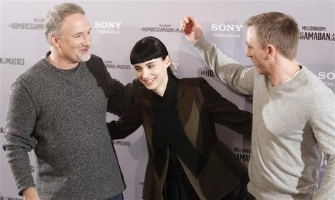 "Cast members Craig and Mara pose with director Fincher during the media presentation of their movie ""The Girl with the Dragon Tattoo"" in Mad"