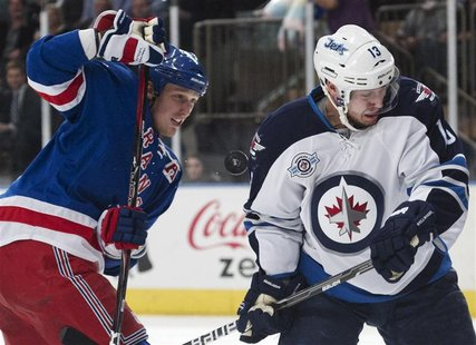Winnipeg Jets' Wellwood reacts in front of New York Rangers' Staal as he is hit by a puck during their NHL ice hockey game in New York