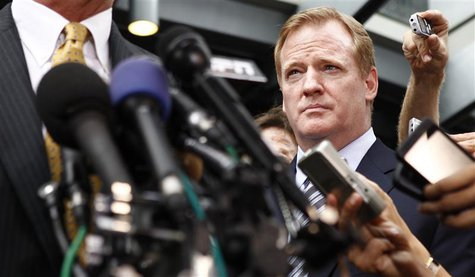 NFL Commissioner Roger Goodell listens to remarks outside the NFL Players Association Headquarters in Washington
