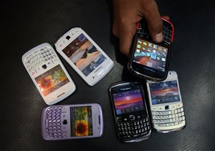 A salesman displays a Blackberry mobile phone to customers next to dummy handsets at a shop in Jammu