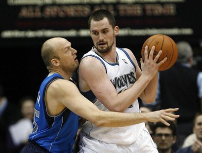 Timberwolves forward Love drives against Mavericks forward Cardinal in Minneapolis