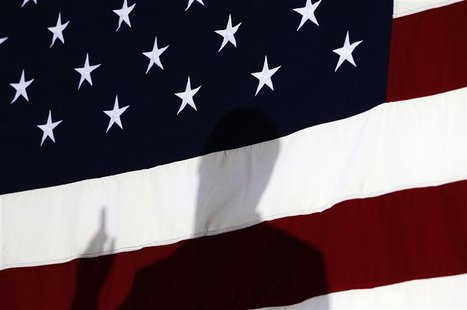 Republican presidential candidate and former Speaker of the House Newt Gingrich is silhouetted against the U.S. Flag during his speech at a