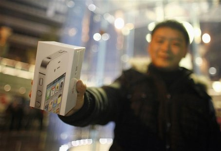 A customer show his iPhone 4S after making the purchase at Apple's retail store in downtown Shanghai