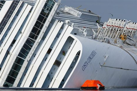 Firefighter rescuers work on the cruise liner Costa Concordia, which ran aground off the west coast of Italy at Giglio island