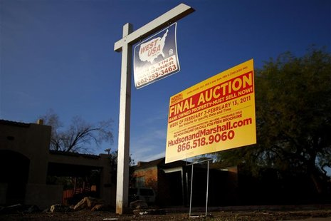 A realtor and bank-owned sign is displayed near a house for sale in Phoenix