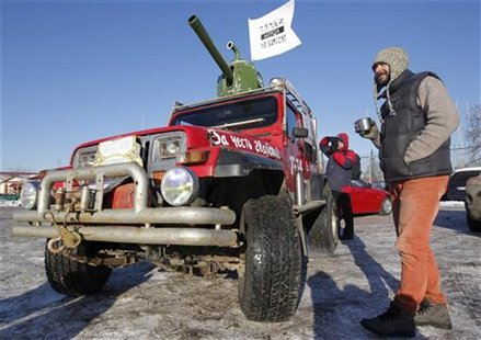 "A participant stands near his car, which was modified to resemble a tank, before taking part in ""The White Ring"", a protest motor rally in M"